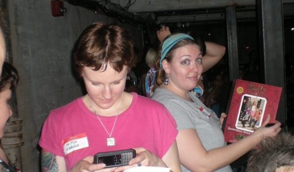 "Showing off the ""yearbook."" That's Rebecca in the pink, texting her Sunnydale expert for trivia help."